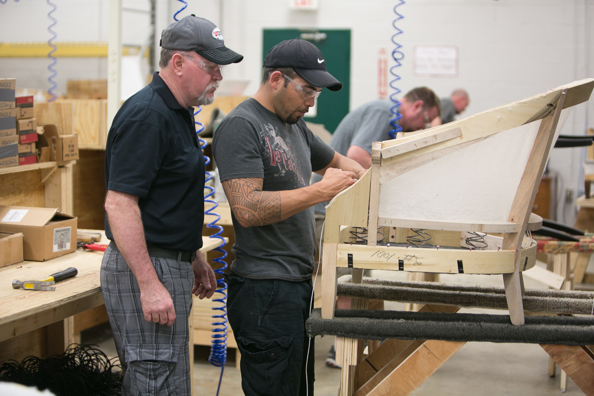 An instructor guides a student CVCC's Furniture Academy.